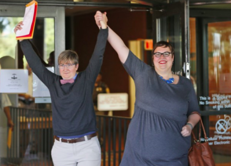 Nicole Pries, left, and Lindsey Oliver hold up their marriage license as they celebrate being one of the first same-sex couples in Virginia to be married outside a Richmond court building. Photo Credit: Steve Helber/AP
