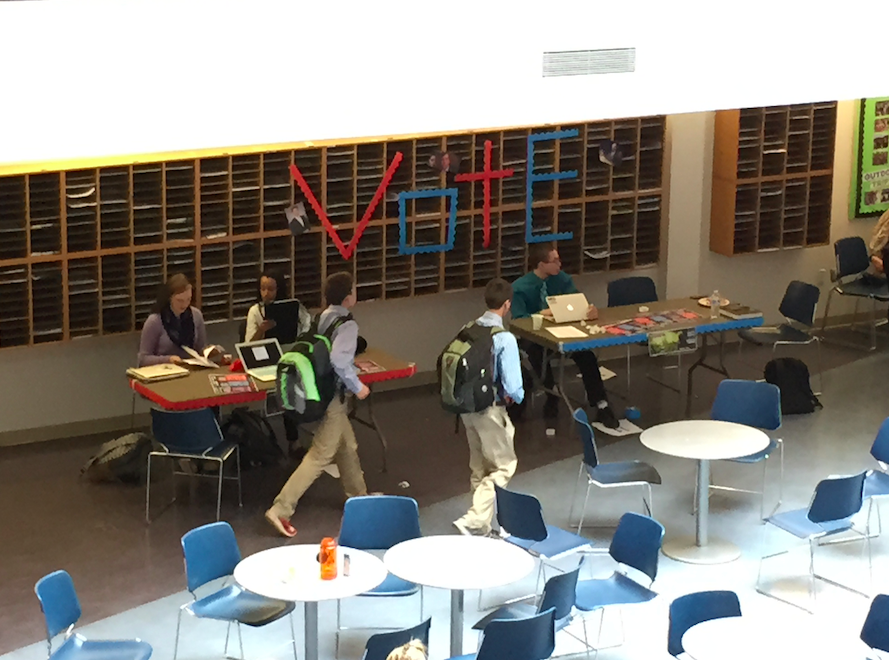 Students pass by the voting booth in the commons on November 4, 2014, in a mock election.