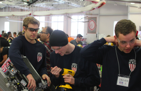 Members of senior team 6652 make last-minute changes to their robot to fit the size restriction and prepare for their first match. (From left: Eddie Dean, Ben Letowt, and Scott Hamal) Photo Credit: Michael Snyder