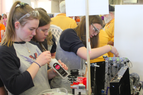 Members of Team 6341 respond quickly and efficiently to a mid-competition setback, and succeed in patching the robot up to perfect working condition. (From left: junior Hailey Scherer, sophomore Giana Fiore, and junior Cailin Mazan.) Photo credit: Michael Snyder