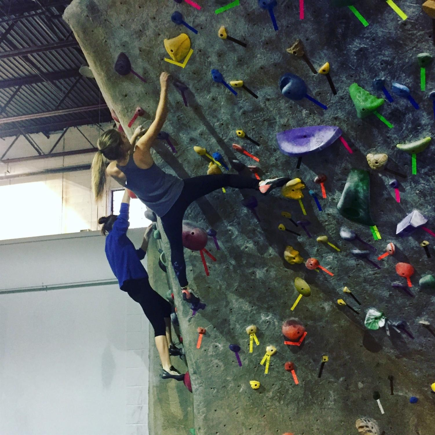 Junior Lily Lindquist carefully climbs a difficult wall.