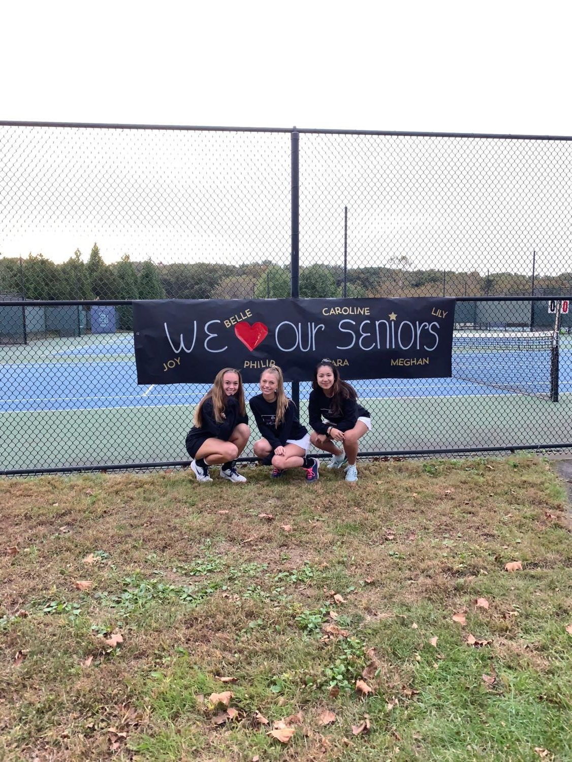 Seniors Caroline Dycio (left), Meghan Golden (middle), and Belle Ditthavong (right) pose in front of the poster team parents made honoring the seniors on the Girls' Varsity Tennis team.